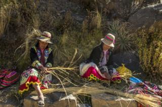 Women weave the thin ropes that are joined to make the larger ones used on the bridge