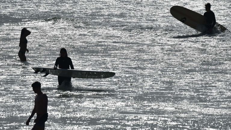 Surfers enjoy the warm weather in Bournemouth, Dorset