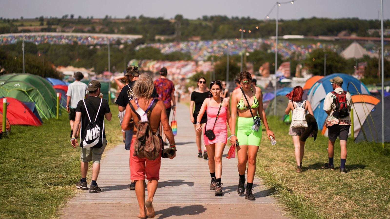 Festival goers walk through a campsite during hot weather at Glastonbury Festival in Somerset