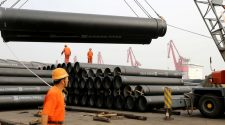 © Reuters. Workers direct a crane lifting steel pipes for export at a port in Lianyungang, Jiangsu