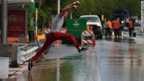 A man tries to jump to a shallow spot while crossing a flooded street on Miami Beach during the 2015 king tide floods.