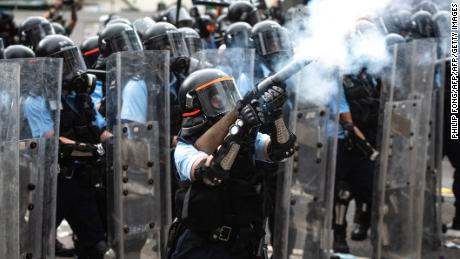 A police officer fires tear gas during clashes with protesters during a rally against a controversial extradition law proposal outside the government headquarters in Hong Kong on June 12, 2019.