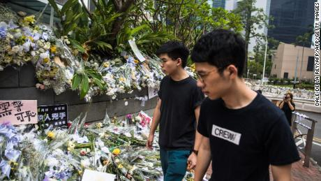 Hong Kong pro-democracy activist Joshua Wong (left), who was just released from jail, walks past flower tributes at a makeshift memorial site for a protester who fell to his death while hanging banners against a controversial extradition law proposal on June 15, in Hong Kong on June 17, 2019.