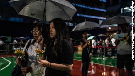 People hold flowers in the rain ahead of a memorial service on July 11, 2019, in Hong Kong, for a protester who died.