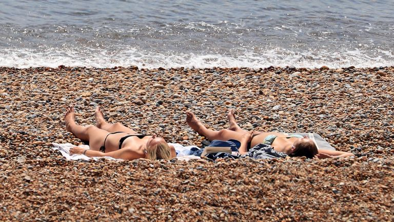 Sunbathers relax in the sunshine on the beach in Folkestone, Kent, as the UK is expected to edge towards its hottest ever July day, with the mercury due to soar above 30C (86F).