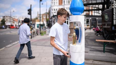 A boy fills a water bottle as temperatures rise in London on Monday.
