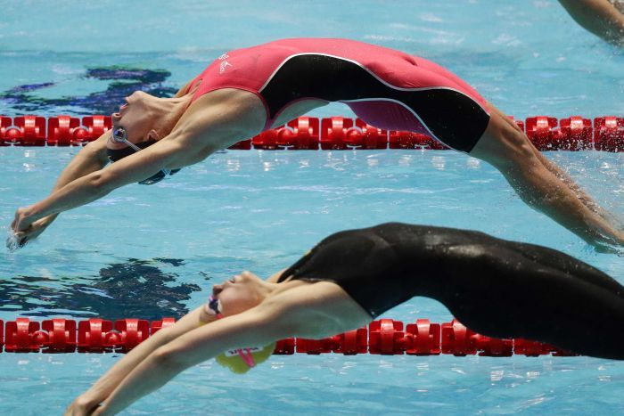 Two women jump drive backwards into a pool side by side.
