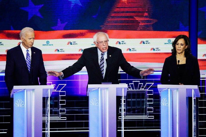 From center, Vermont Sen. Bernie Sanders speaks while former Vice President Joe Biden and Sen. Kamala Harris look on during the second night of the first Democratic presidential debate on Thursday in Miami.