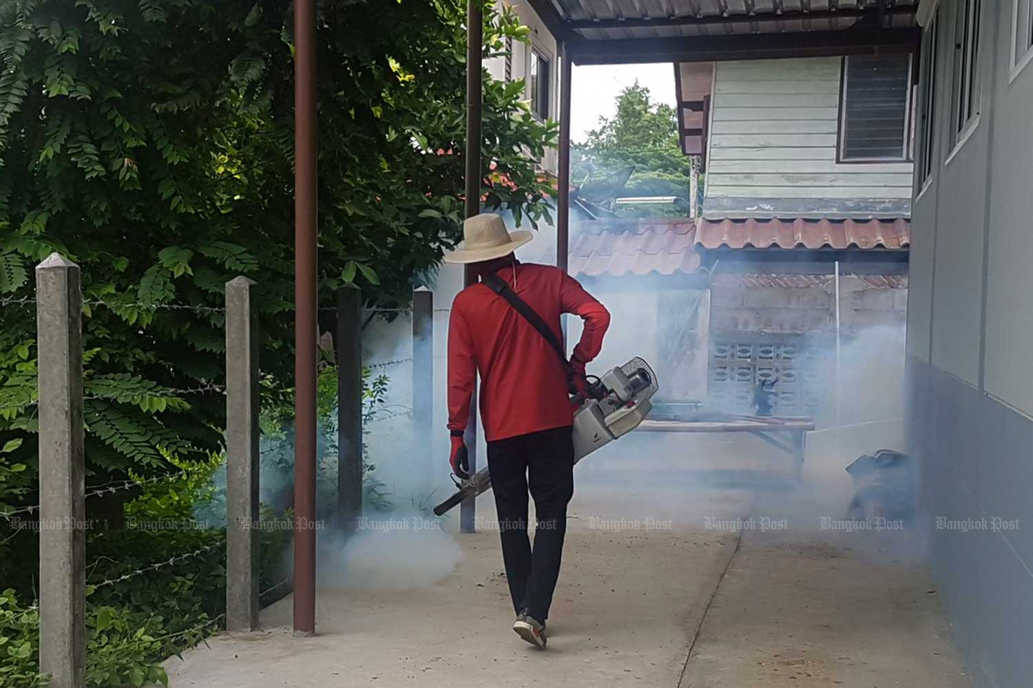 A health volunteer sprays smoke during an anti-malaria fumigation drive in Phimai district, Nakhon Ratchasima. (Bangkok Post photo)