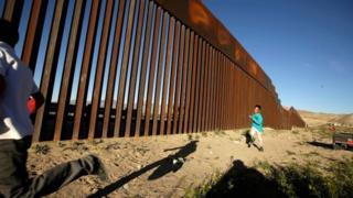 Children run along the border fence between Mexico and the United States during an inter-religious service against US President Donald Trump's border wall in Ciudad Juarez, Mexico, on 26 February 2019