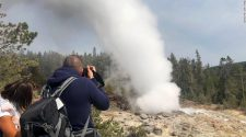 Tourists watch the Steamboat Geyser erupt on August 22, 2018, in Yellowstone National Park.