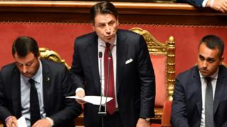 Italy's Prime Minister Giuseppe Conte addresses the Senate flanked by Matteo Salvini (L) and Luigi Di Maio