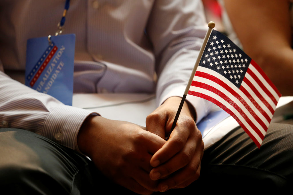 A new citizen holds a U.S. flag at the U.S. Citizenship and Immigration Services (USCIS) naturalization ceremony at the New York Public Library in Manhattan, New York, U.S., July 3, 2018. REUTERS/Shannon Stapleton