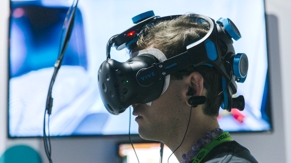 Man wearing VR headset with wires attached