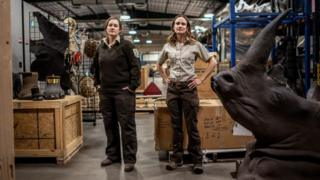 Elisa Dahlberg and Sarah Metzer surrounded by items such as turtle shells, elephant feet, a dead rhino head and much more