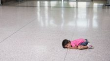 A young migrant girl sits on the floor as her father, recently released from federal detention with other Central American asylum seekers, gets a bus ticket at a bus depot on June 11, 2019, in McAllen, Texas.