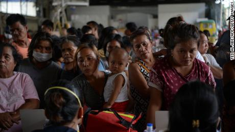 Evacuees from towns affected by the eruption of Taal volcano queue up to have their children checked by medical personnel at an evacuation center in Tanauan town, Batangas province.