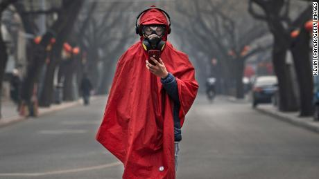 A Chinese man wears a protective mask as he stands in a nearly empty street in Beijing on January 26.