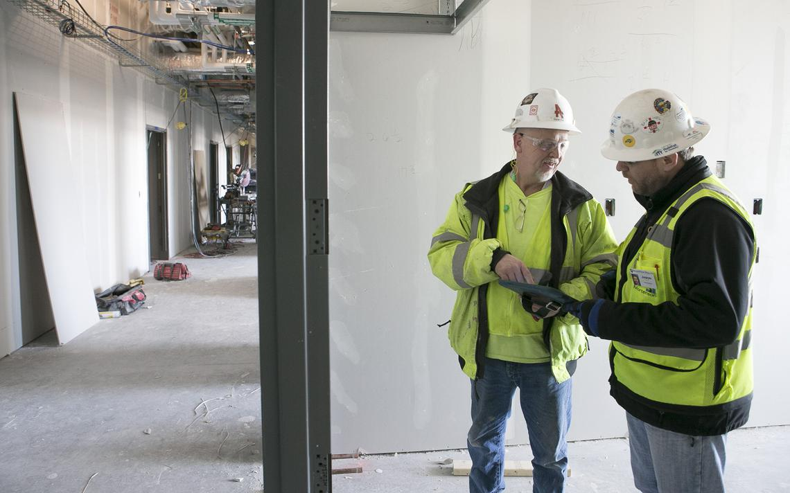 Carpenter foreman Steve Ives, left, and Mortenson's Construction project manager Jason Toso compare notes at the site of the RiverView Health Clinic and Hospital, under construction in Crookston. Photo by Eric Hylden/Grand Forks Herald