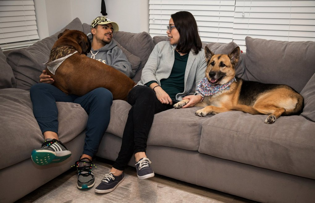Alex and Andrea Sosias with dogs Amino, left, and Lola at home in Gaithersburg, Md. (Evelyn Hockstein / Photo for The Washington Post)