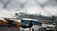 A bus driven by a chauffeur in protective gear departs the dock occupied by the quarantined Diamond Princess.  Eleven passengers who are elderly or have pre-existing medical conditions were removed from the ship Friday and will finish out their quarantine on shore in Japan.