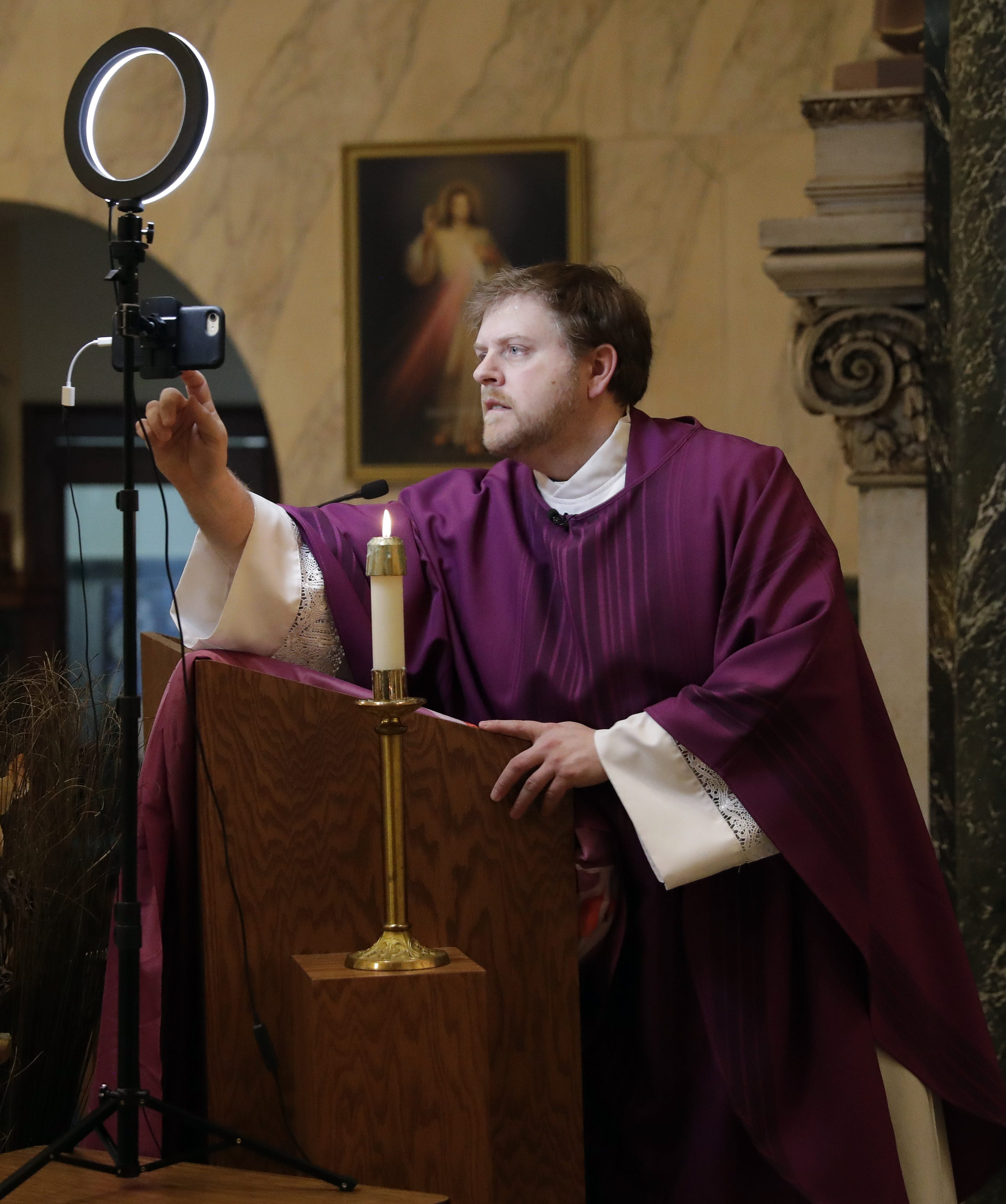 """The Rev. Brian Wideman presses """"record"""" on his phone before giving his homily in front of an empty St. Paul Catholic Church on March 21, 2020, in Wrightstown, Wis. Wideman began recording masses for St. Clare Parish after church services were suspended to the public because of the coronavirus pandemic."""