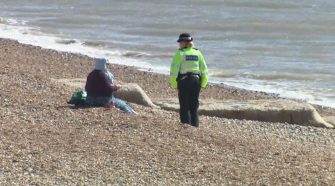 A police officer speaks to a woman sitting on beach at Brighton during lockdown