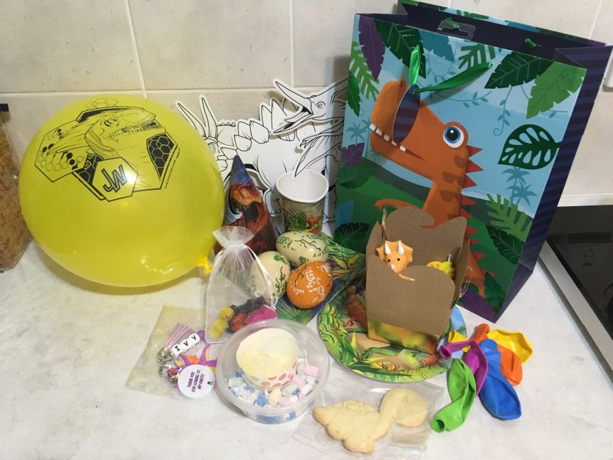 A dinosaur gift bag with other dinosaur party favours, yellow balloon and cookie.