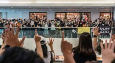 Anti-government protesters wearing protective masks sing songs and make gestures during a demonstration at a shopping mall today. Since the worst of the current coronavirus pandemic has passed, new anti-government protests have recently started to reappear in Hong Kong