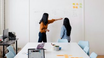 two women pointing at a whiteboard, with a table and a laptop in the foreground