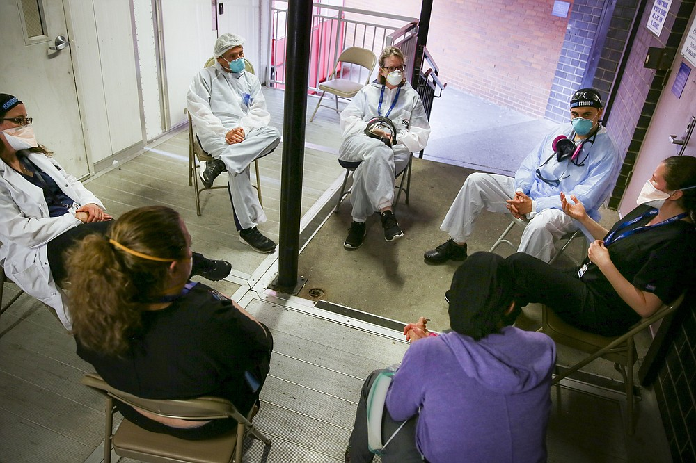 Hospital workers sit for a group counseling session at Elmhurst Hospital to talk about their experiences dealing with the COVID-19 pandemic, Friday, May 29, 2020, in New York. At hospitals around the country, nurses, doctors and other health care workers are reckoning with the psychological toll of the virus fight, coupled with fears that the disease could flare anew later this year. (AP Photo/Robert Bumsted)