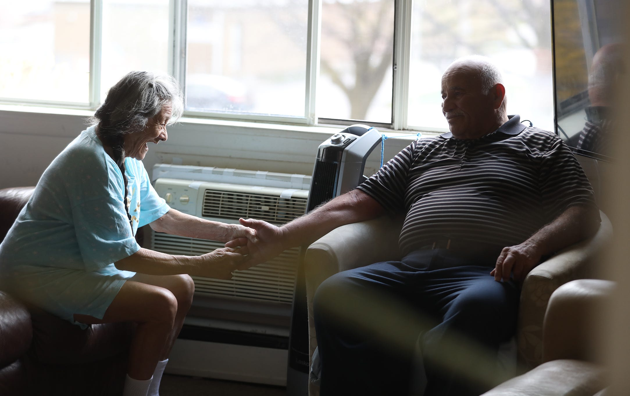 Maria Rodriguez, who has dementia and diabetes, has memory loss but always smiles when she sees her husband of 59 years, Angel Moreno.  Rodriguez sits down the living room, Wednesday, April 15, 2020 and starts holding her husband's hand and shaking it.  The couple's daughters Nancy and Carmen Moreno are always at their Irondequoit apartment helping out.