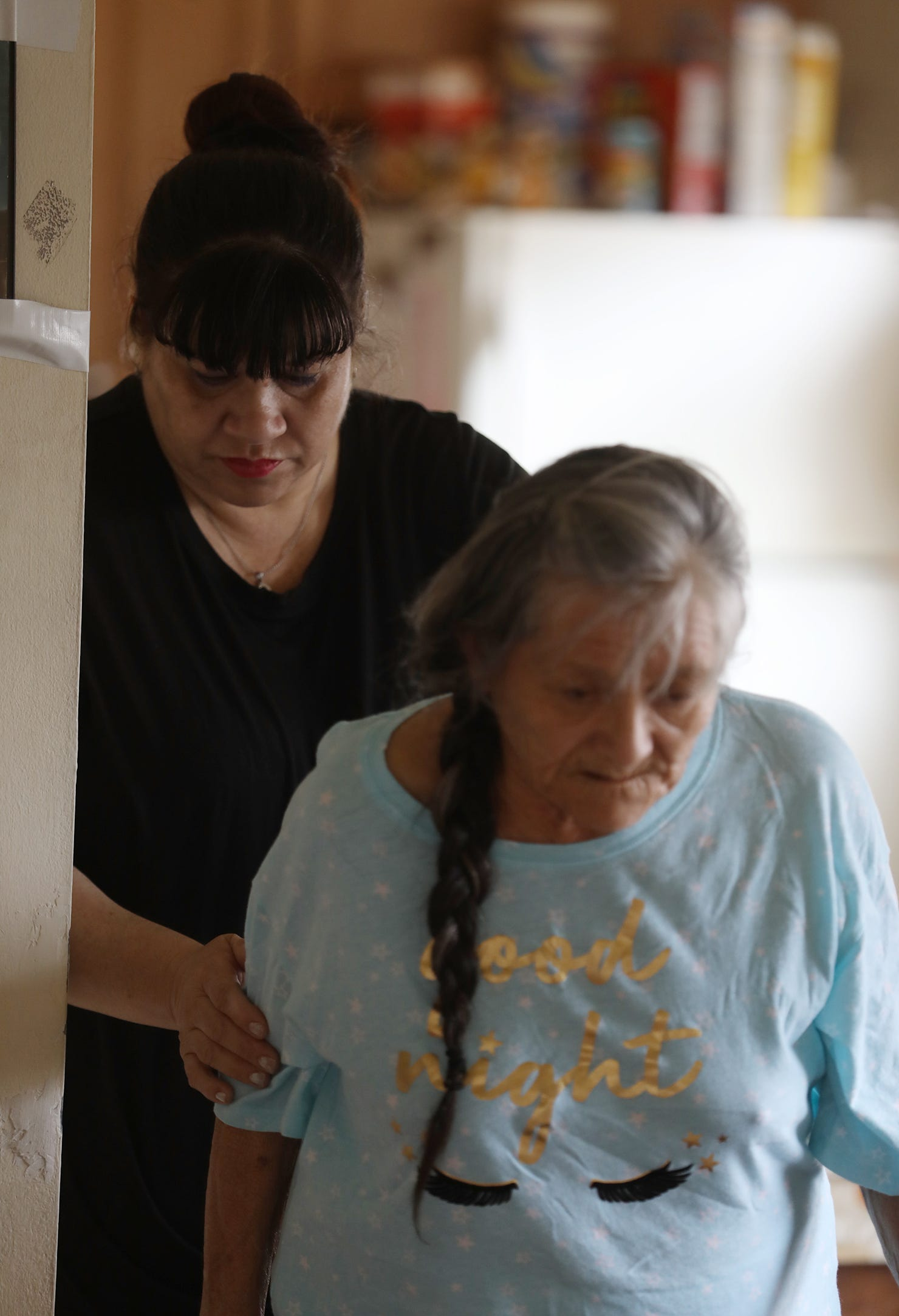 Carmen Moreno helps her mother, Maria Rodriguez, into the living room after feeding her a snack, Wednesday, April 15, 2020.  She and her sister, Nancy Moreno. share caretaking of their mother, who has dementia and diabetes, and their father, Angel Moreno.