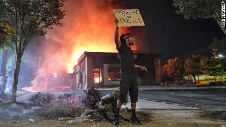 A person holds a sign as a Wendy's restaurant burns Saturday in Atlanta