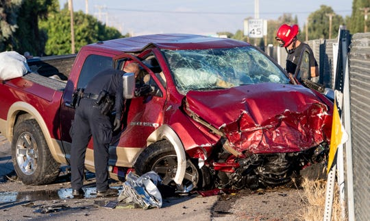Visalia Police and Fire departments investigate a deadly head-on collision on Mineral King Avenue at Crumal Street on Monday, July 6, 2020. The truck left westbound Highway 198 through chain-link fence about a half-mile before striking the eastbound car. Both occupants of the car died at the scene, the driver of the truck was transported to a local hospital.