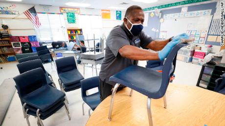 Des Moines Public Schools custodian Tracy Harris cleans chairs in a classroom at Brubaker Elementary School.