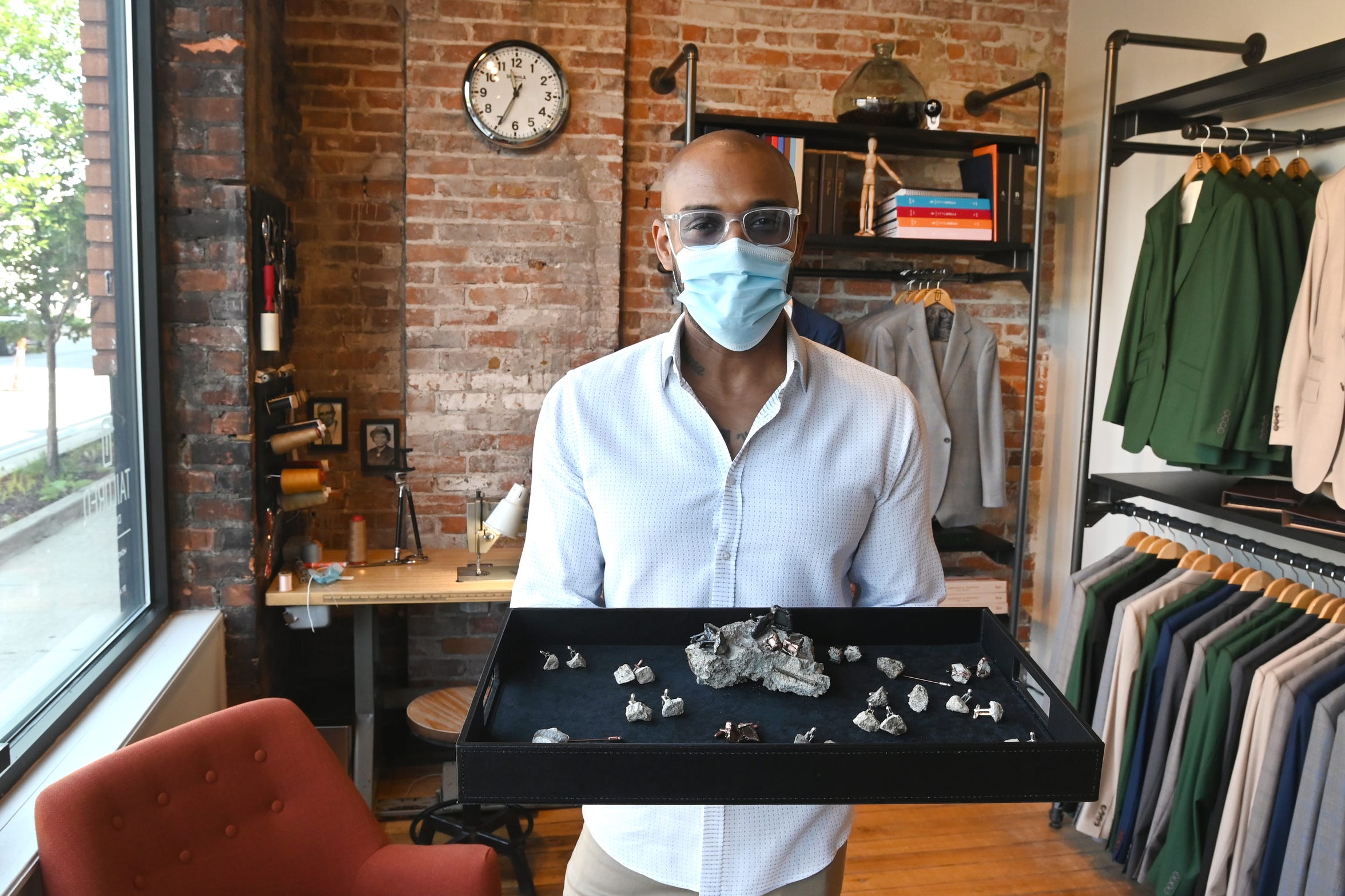 Warick Richardson, owner of Tailored Detroit, shows the commissioned cufflinks and lapel pins made from the concrete and broken glass from chunks from a thwarted burglary attempt at his Eastern Market clothing shop.