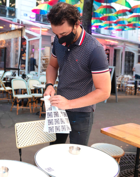 A waiter sticks the QR code in order for customers to download the menu as the terrace is being set up at Les Marronniers Cafe in Paris, France.