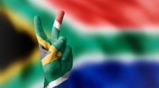 South African flag in the colours red, blue, black, green, gold and white in the background and painted on a person's hand who is holding a peace sign.