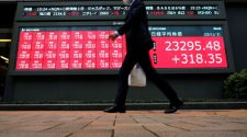 © Reuters. A man wearing a protective face mask walks past a stock quotation board outside a brokerage, amid the coronavirus disease (COVID-19) outbreak, in Tokyo