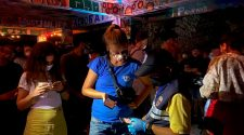 In this Tuesday, Jan. 26, 2021 photo, a Thai immigration officer talks to people at a bar on Koh Phangan island, Surat Thani province, southern Thailand. Police raided a party at a bar on a popular resort island in southern Thailand and arrested 89 foreigners for violating coronavirus regulations, officials said Wednesday. Pic: AP