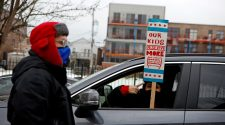 English Language Program teacher Marlon Henriquez and bilingual teacher at Pilsen Community Academy Daniela Lugo prepare for a car caravan of supporters of the Chicago Teachers Union, as negotiations with Chicago Public Schools continue over a coronavirus disease (COVID-19) safety plan agreement in Chicago on Jan. 30. REUTERS/Eileen T. Meslar/File Photo