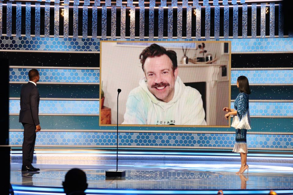 BEVERLY HILLS, CALIFORNIA: 78th Annual GOLDEN GLOBE AWARDS -- Pictured: Jason Sudeikis (c) accepts the Best Television Actor – Musical/Comedy Series award for 'Ted Lasso' via video from Sterling K. Brown (l) and Susan Kelechi Watson onstage at the 78th Annual Golden Globe Awards held at The Beverly Hilton and broadcast on February 28, 2021 in Beverly Hills, California. -- (Photo by Christopher Polk/NBC/NBCU Photo Bank via Getty Images)