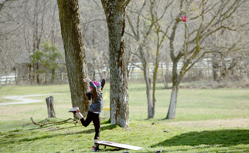 Marc Hayot/Herald-Leader Sarah Thompson takes a break from biking to play a game of Corn Hole. The game was provided by the American Legion. Thompson scored the goal.
