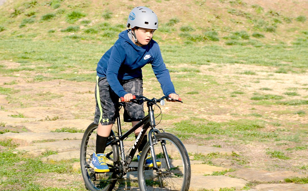 Marc Hayot/Herald-Leader Jaydon Boles pumps the peddles on his bike as he rides the wooden course at City Lake Park during Spring Break Bike Fest. Boles is the son of Park and Recreation Manager Jon Boles.