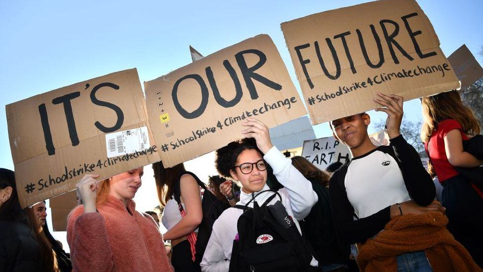 """Climate change protesters holding a sign saying """"It's our future"""""""